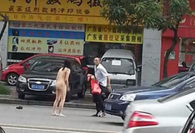A couple having an intense argument were spotted removing their clothes along a busy street in Dongguan, in China's Guangdong Province.