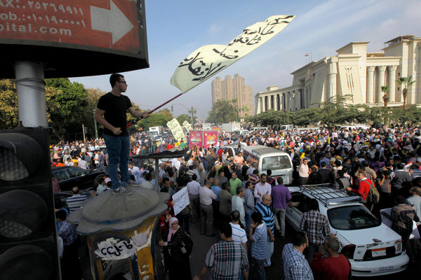 "A Mohamed Morsi supporter waves a flag that reads ""No to the coup"" outside the Supreme Constitutional Court in Cairo."