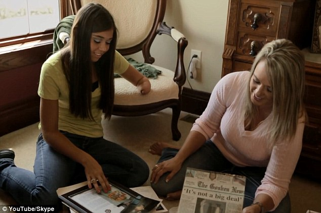 History: Sarah looks through news clippings with her mother. Her family reached out to Paige's parents because of the girls' disability.