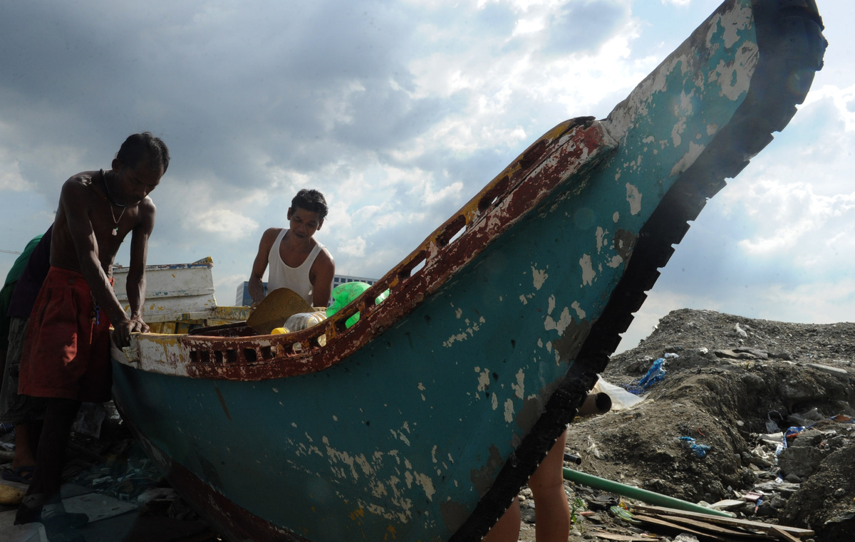 Fisherman repair there outrigger on the shore of Manila bay as Typhoon Haiyan approached on November 7, 2013. (JAY DIRECTO/AFP/Getty Images)