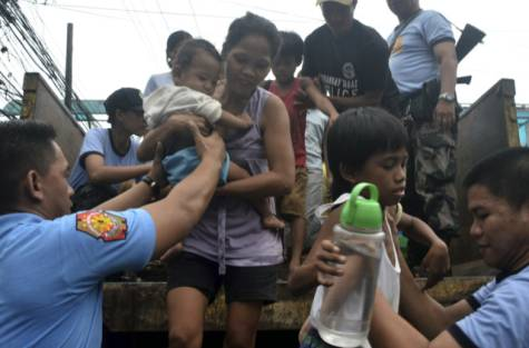 Residents living near the slopes of Mayon volcano are evacuated to public schools by police in anticipation of the powerful typhoon Haiyan that threatened Albay province and several provinces in central Philippines Thursday afternoon Nov.7, 2013.