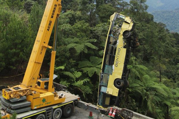 Filepix shows the bus being hoisted out of the ravine