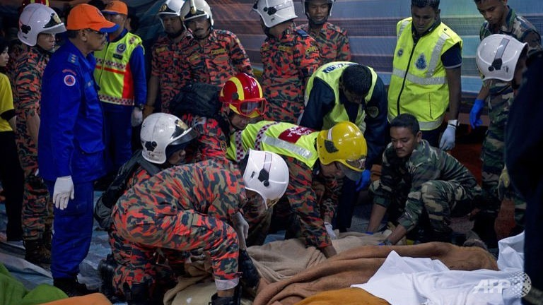 File photo: Malaysian rescuers attend to the bodies of bus passengers killed in an accident near Genting Highlands, on August 21, 2013. (AFP/Mohd Rasfan)