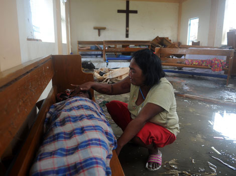 A mother weeps beside the dead body of her son at a chapel in the aftermath of Super Typhoon Haiyan in Tacloban, eastern island of Leyte.