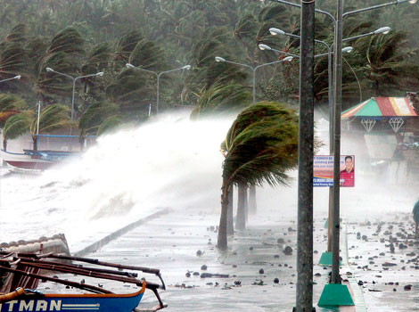 A resident walks past high waves pounding the sea wall amidst strong winds as Typhoon Haiyan hit the city of Legaspi, Albay province, south of Manila. (AFP photo)