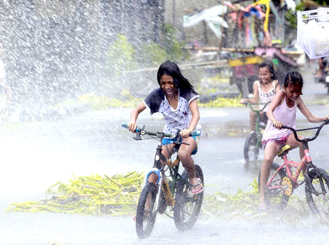 Girls ride on bicycles as they are splashed with water from strong waves in a coastal village as Typhoon Haiyan battered Bayog town in Los Banos, Laguna, south of Manila November 8, 2013. (Reuters)