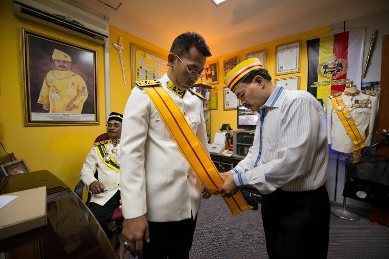"Self-styled royal Raja Noor Jan Shah Raja Tuah Shah (R) adjusts an official dress for title ""Datuk"" at his palace ahead of a private function in Gombak, on the outskirt of Kuala Lumpur, on September 7, 2013. (AFP Photo/Mohd Rasfan)"