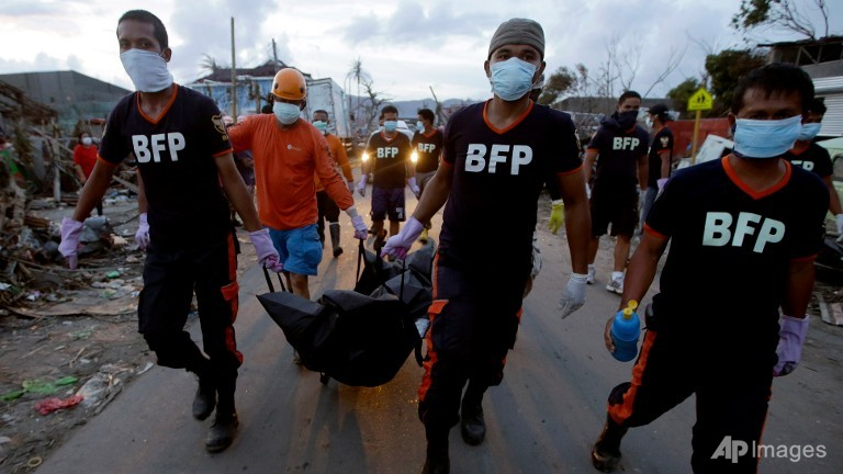 Firemen carry the body of a victim of Typhoon Haiyan in Tacloban, central Philippines. (AP/Dita Alangkara)