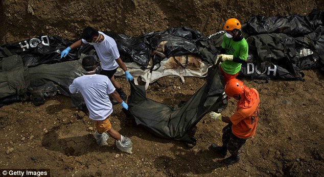 Volunteers drag the corpses into place in storm-hit Tacloban.