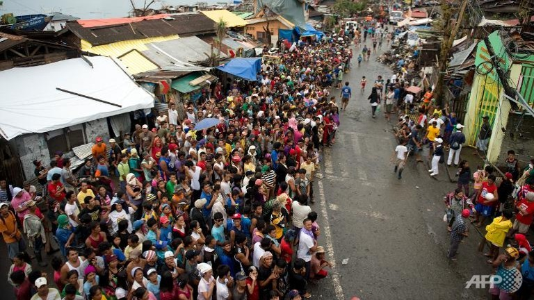 Victims of Super Typhoon Haiyan queue for food aid to be distributed in Tacloban on Nov 23, 2013. (AFP/Odd Andersen)