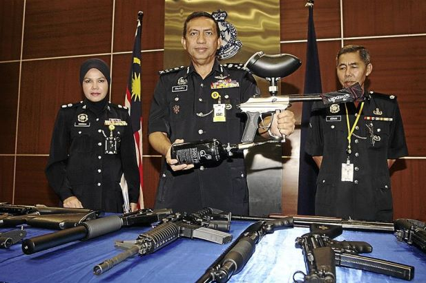 Sticking to their guns: Comm Zulkifli (centre) holding up a paintball marker during the press conference. With him is Supt Norsiah (left). Photo from The Star.