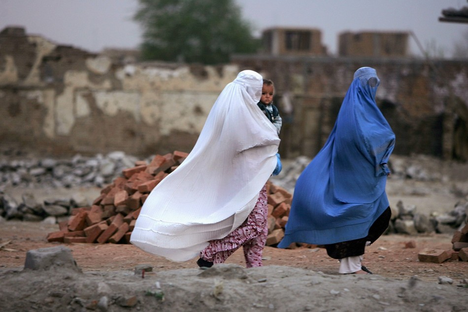 Afghan women walk along a road in the early morning hours in Kabul. An Afghan woman was stoned to death for adultery