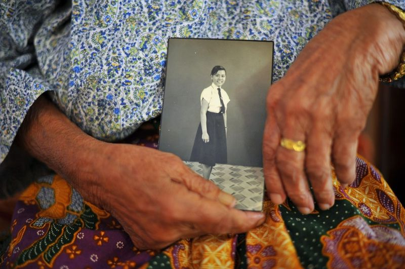 Siti Aishah's oldest sister holding a photo of her as a young child.