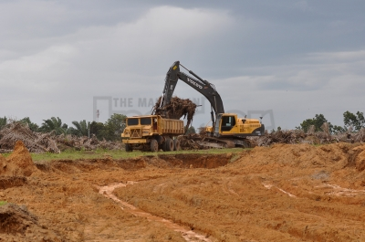 An excavator and a lorry seen clearing what used to be the site of candi number 11, which was destroyed, in Bujang Valley, Kedah.