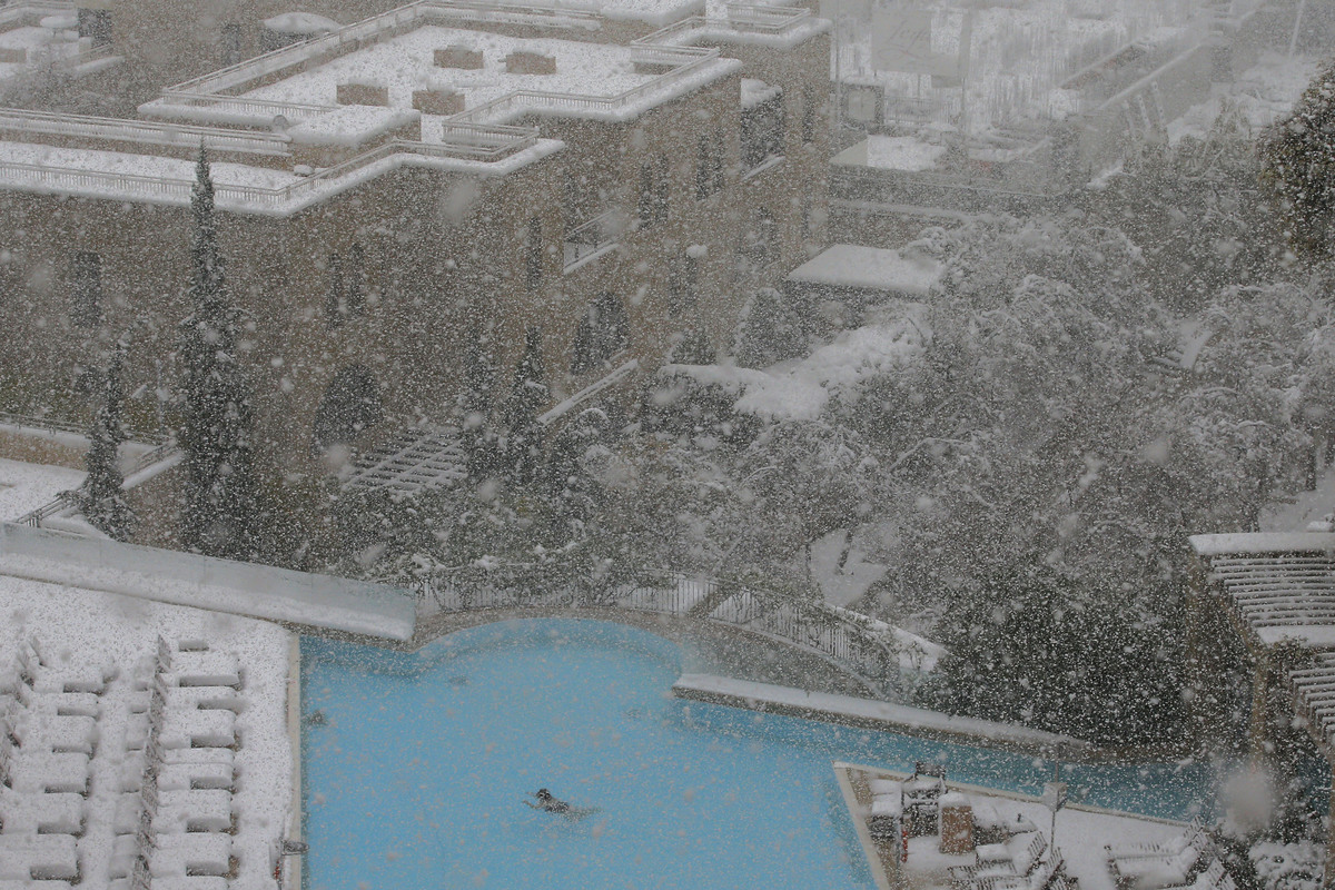 A woman swims in the pool at the David Citadel Hotel during a snowstorm in Jerusalem Friday, Dec. 13, 2013.