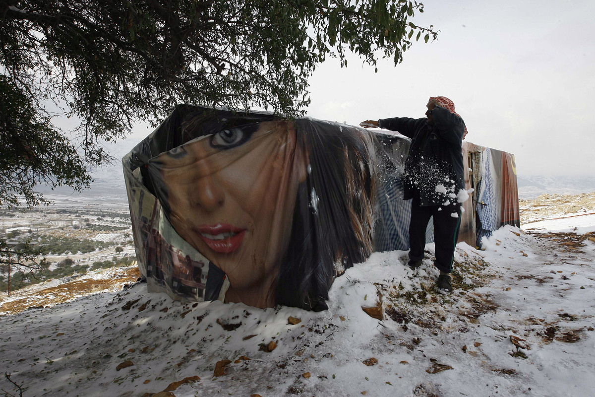 A Syrian refugee man removes snow from the roof of his tent in a camp for Syrians who fled their country's civil war, in the Bekaa valley, eastern Lebanon, Thursday, Dec. 12, 2013.