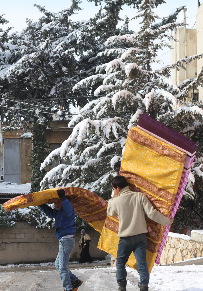 Two Syrian youths carry mattresses to a refugee centre in the eastern Lebanese city of Baalbek in the snow-covered Bekaa Valley on December 12, 2013.