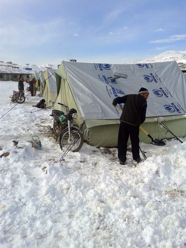 A Syrian refugee shovels snow following a storm in the town of Arsal in the Lebanese Bekaa valley on December 12, 2013.