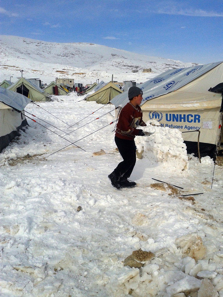 A young Syrian plays with snow following a storm in the town of Arsal in the Lebanese Bekaa valley on December 12, 2013.