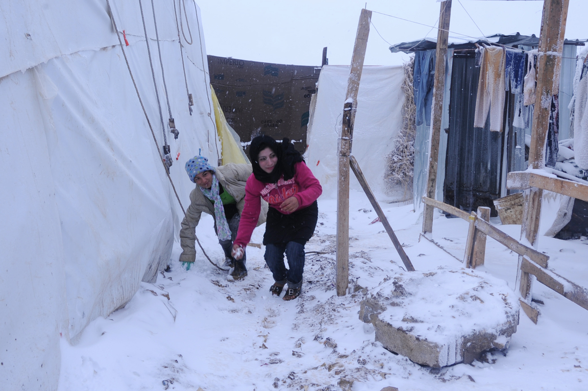 Syrian refugees play with snow at the makeshift refugee camp of Terbol near the Bekaa Valley town of Zahleh in eastern Lebanon on December 11, 2013.