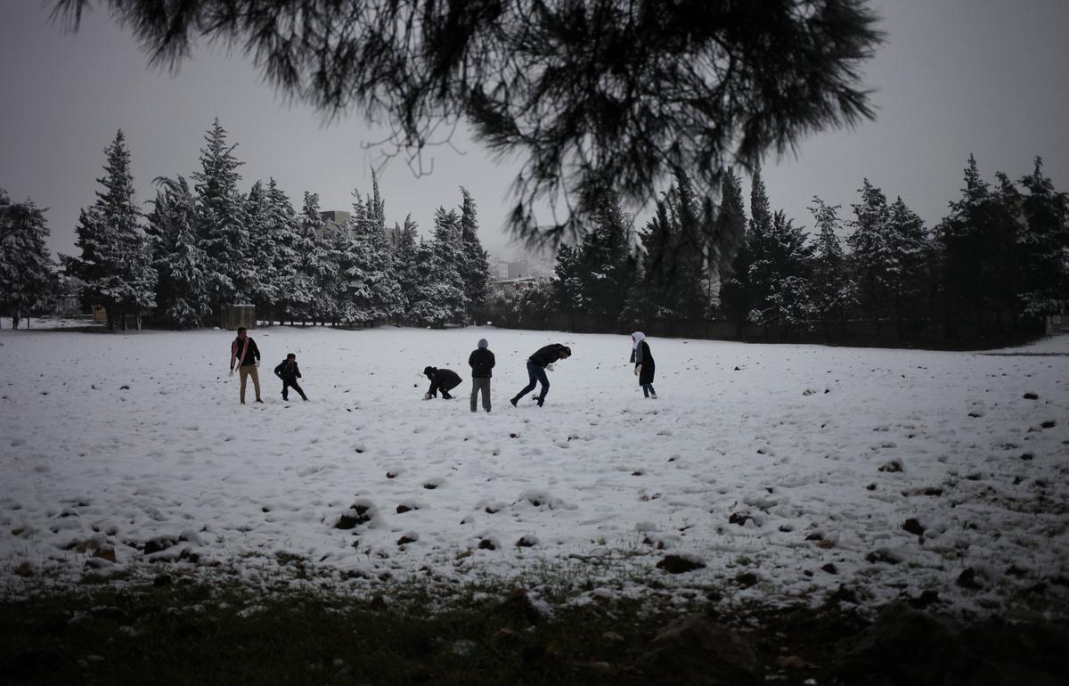 Jordanians play with the snow in an open field during a snowstorm in Amman, Jordan, Thursday, Dec. 12, 2013.