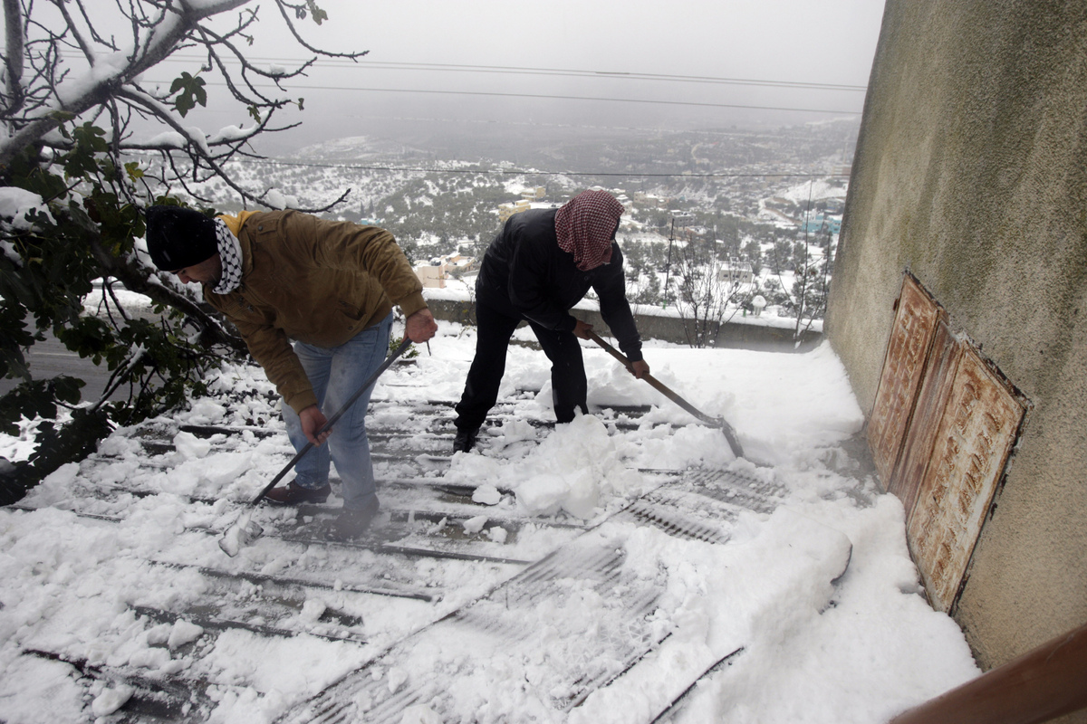 Palestinians move the snow from there home roof in the West Bank village of Seelat Al-Daher near Jenin city, Friday, Dec. 13, 2013.