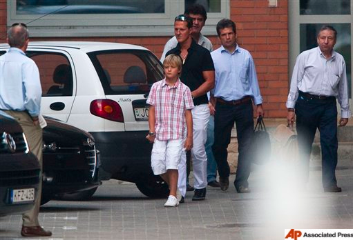 A photo of Michael Schumacher and his son Mick, returning to Michael's car after visiting Ferrari team's Brazilian driver FElipe Massa on Saturday, 1 Aug 2009.