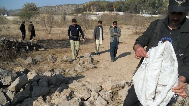 Security personnel examine the site of a sucide bombing in the Ibrahimzai area of Hangu district on January 6, 2014.