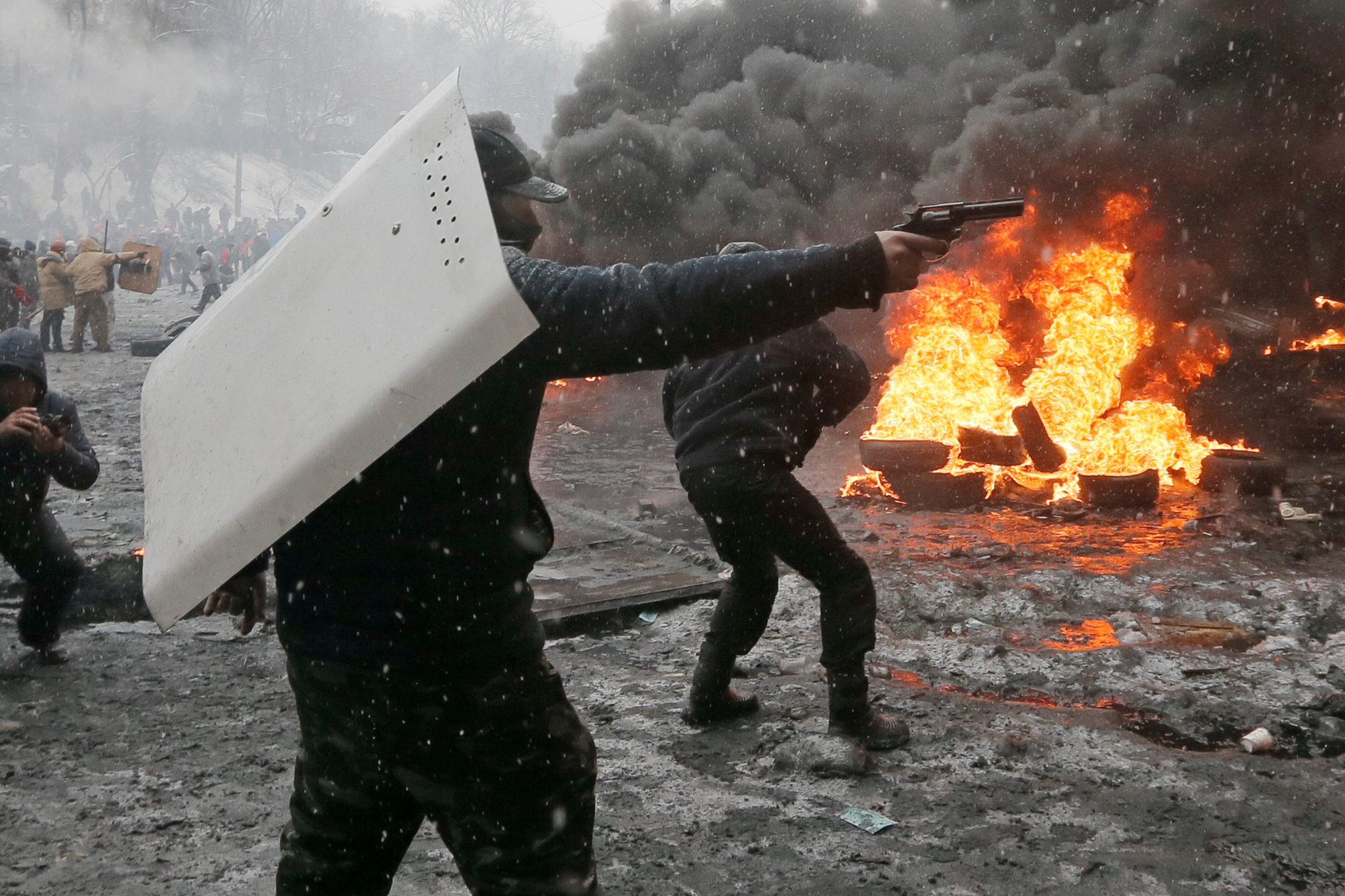 A protester pointed a handgun during clashes with police.