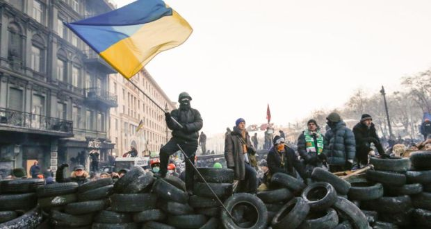 Protesters stand on a barricade during an anti-government protest in Kiev yesterday.