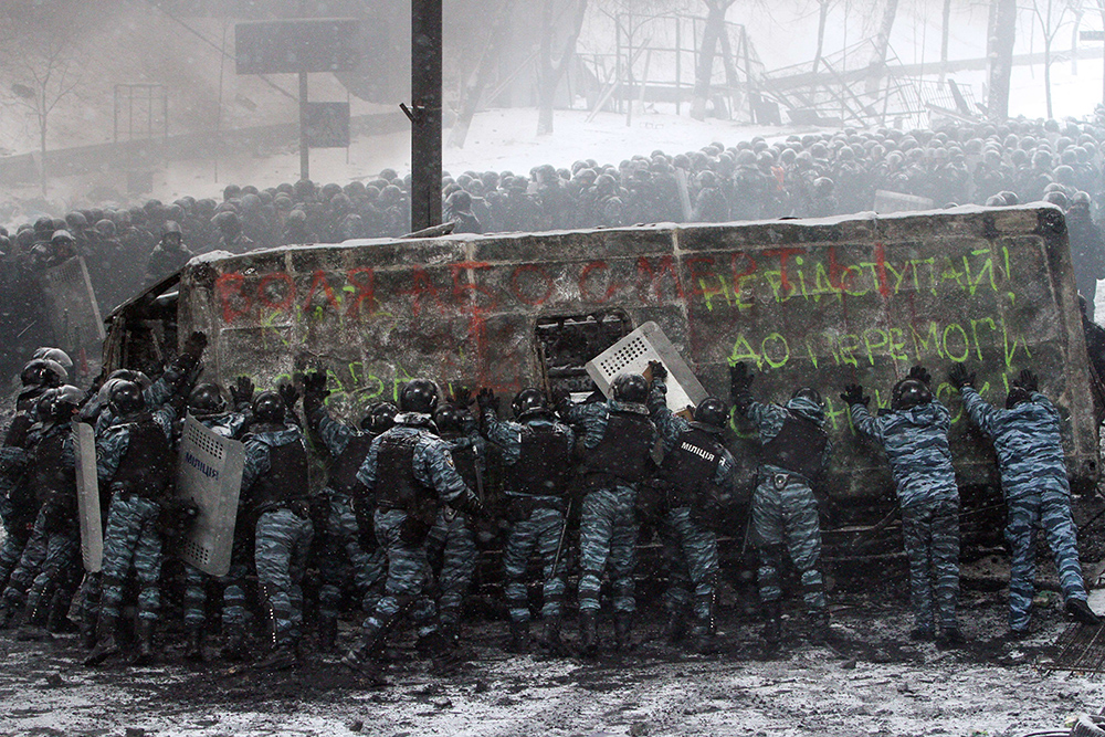 Riot police push a police van destroyed by demonstrators.