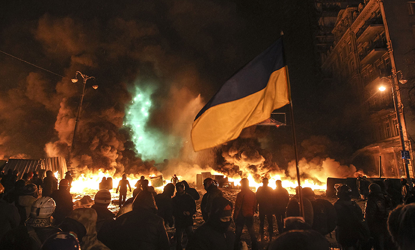 Protesters gather in front of burning tires during clashes with riot police in Kiev.