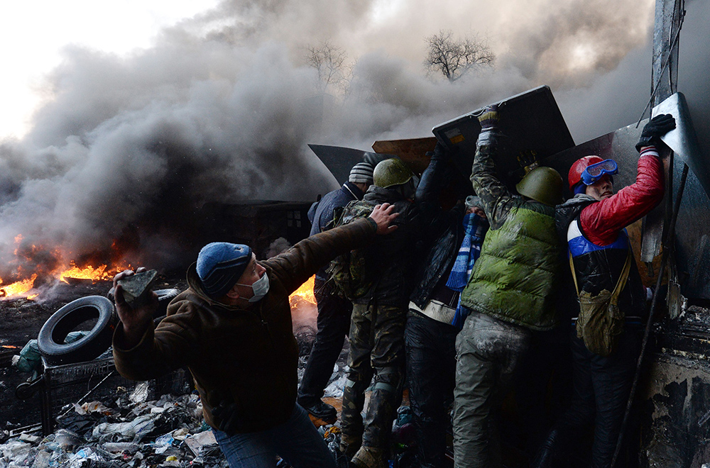 A protester reels back to throw a stone at riot police during clashes