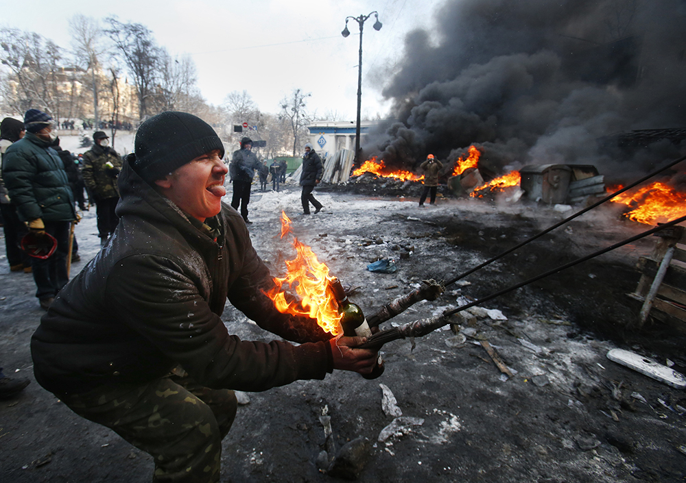 Protesters use a large slingshot to hurl a Molotov cocktail at police in central Kiev.