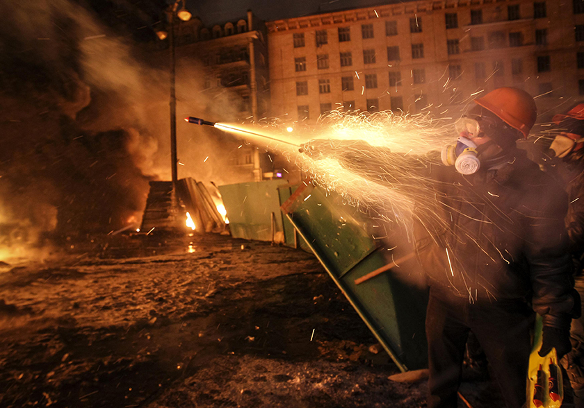 A protester shoots fireworks toward riot police during overnight clashes