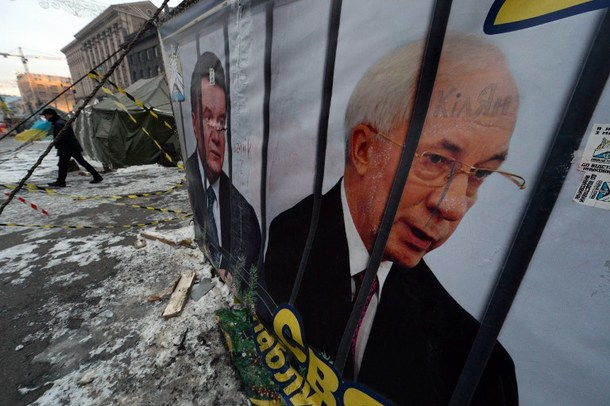 "A man walks past a banner reading ""The holiday is coming. 2014"" and depicting Ukrainian Prime Minister Mykola Azarov (R) and President Viktor Yanukovych behind prison bars at an opposition protester camp on Independence Square in Kiev on January 28, 2014."
