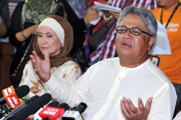Zaid at the press conference with his wife looking on.