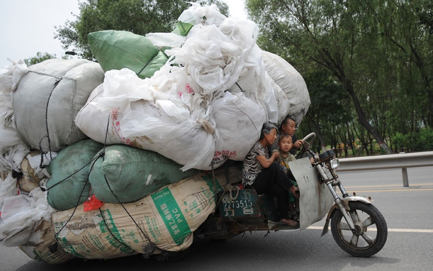 A family ride a heavily overloaded motor tricycle in Taiyuan.