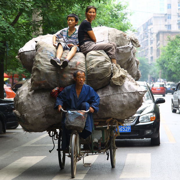 A recyclable materials collector rides a motor tricycle overloaded with huge bags of waste - and his wife and son - along a street in Xi'an.