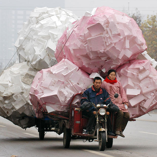 A man and a woman ride a motor tricycle carrying bags of recyclable polystyrene in Shouguang.