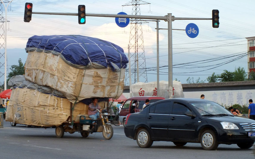 A man rides an overloaded motor tricycle on a busy street in Beijing.