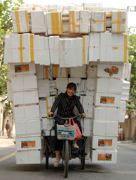 A woman rides a tricycle carrying polystyrene boxes in Shanghai.