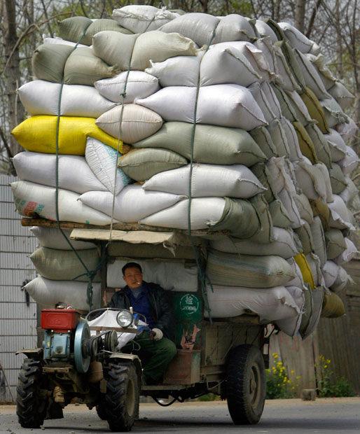 A man drives a tractor carrying bags of rice in Huai'an.
