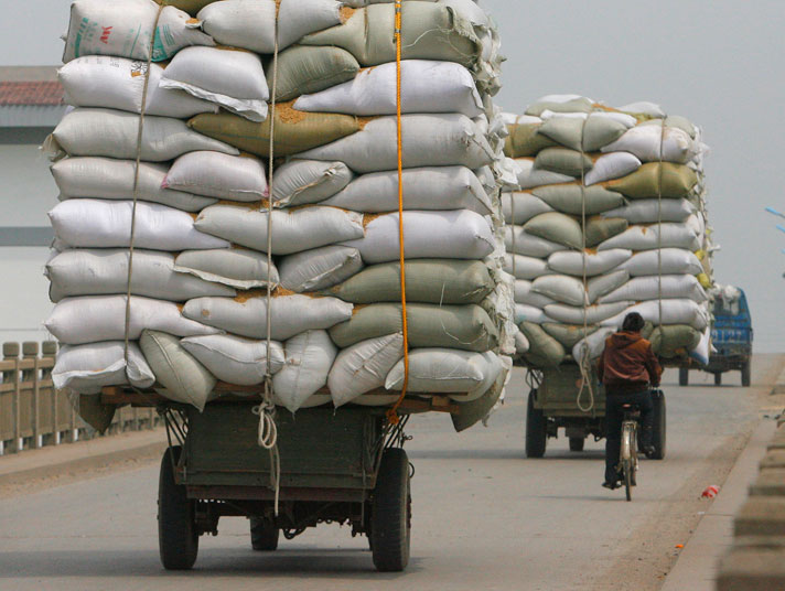 Overloaded trucks are driven along 204 national highway in Hai'an.