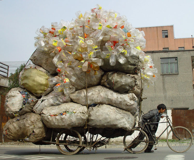 A collector pushes a tricycle loaded with bags of recyclable waste in Shanghai.