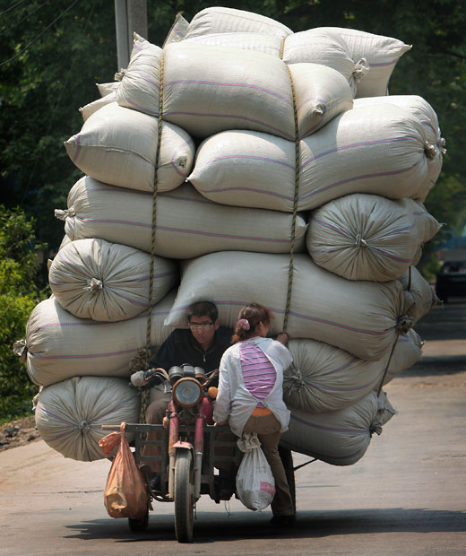 A man and a woman sit on a motor tricycle carrying bags of goods in Nanjing.