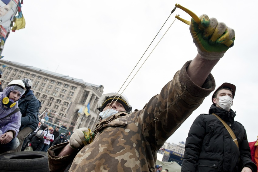 An anti-government protester uses a slingshot to throw stones towards riot police on Feb. 19, 2014.