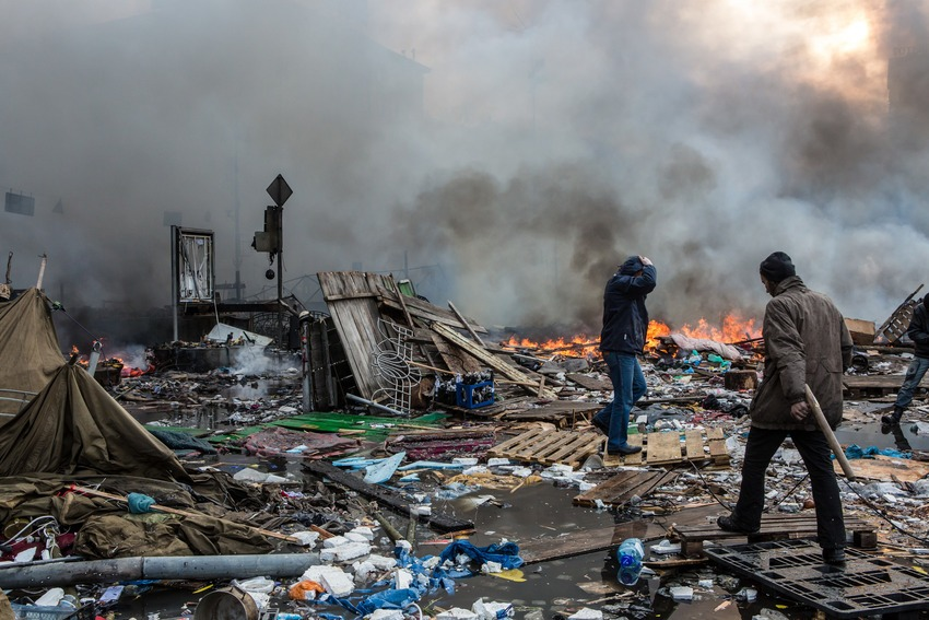 Anti-government protesters walk amid debris and flames near the perimeter of Independence Square, known as Maidan, on Feb. 19, 2014.