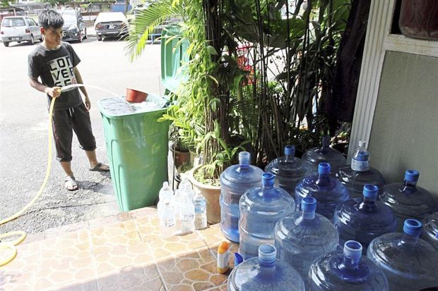 Taman Setia Balakong Apartment resident Muhammad Izzani Islahudin, 15, filling up containers of water after supply was restored Thursday.
