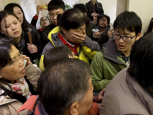 A woman, center, surrounded by media covers her mouth on her arrival at a hotel which is prepared for relatives or friends of passengers aboard the missing plane, in Beijing